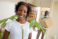 Couple moving house, man carrying box in hallway, woman holding pot plant, smiling, portrait tilt