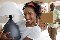 Couple moving house, man carrying box in hallway, woman holding lamp, smiling, portrait