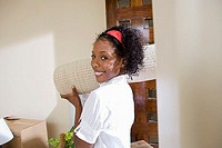 Woman moving house, carrying rolled-up carpet on shoulder in doorway, smiling, side view, portrait