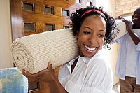 Couple moving house, carrying rolled-up carpet on shoulders through doorway, smiling (thumbnail)