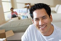 Couple moving house, woman sitting in living room, focus on man in foreground, smiling, portrait
