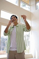 Man standing beside window, holding aloft keys to new house, using mobile phone, smiling