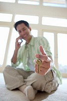 Man sitting on floor, holding keys to new house, using mobile phone, smiling, portrait surface level