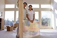Couple moving house, standing in bare living room with rolled-up carpet and picture frame, portrait