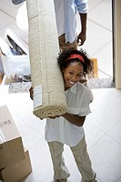 Couple moving house, carrying rolled-up carpet on shoulders through doorway, woman smiling, elevated view