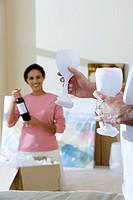 Couple moving house, woman holding bottle of wine in living room, man holding two wine glasses