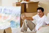 Man moving house, sitting on floor in living room, holding glass of wine, smiling, side view, portrait