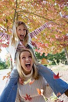 Mother carrying daughter 7-9 on shoulders in park in autumn, girl pulling branch, laughing