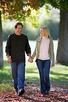 Couple walking in autumn park, holding hands, smiling, front view