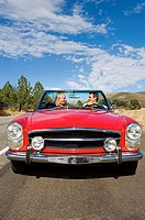 Mature man and adult son driving in red convertible car along country road, smiling, front view