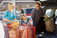 Family loading car boot with groceries in supermarket car park, smiling, side view