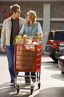 Couple leaving supermarket, woman pushing shopping trolley in car park, smiling, front view