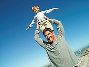 Boy 4-6 standing on father's shoulders at beach, arms out, smiling tilt