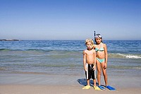 Boy 4-6 and girl 5-7 standing side by side on sandy beach, wearing snorkels and flippers, front view, portrait