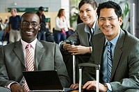 Three businessmen sitting in airport terminal with laptop and luggage, smiling, front view, portrait