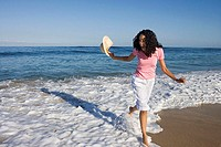 Cheerful woman avoiding Atlantic surf washing on sandy beach, carrying sun hat, laughing