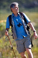 Mature man hiking on mountain trail, carrying rucksack, using hiking pole, front view tilt