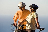 Mature couple, in cycling helmets, standing on clifftop with mountain bikes, Atlantic Ocean in background