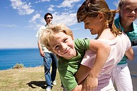 Mother embracing son and daughter 7-9 on clifftop overlooking Atlantic Ocean, father looking on