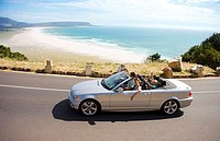 South Africa, Cape Town, family man driving silver convertible car along coastal road, side view