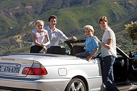 Family standing beside parked convertible car on mountain roadside, smiling, portrait