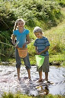 Boy 6-8 and girl 7-9 standing in shallow stream, holding fishing nets, smiling, portrait