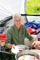 Person serving senior man fried breakfast on camping trip, man sitting inside tent, smiling, portrait