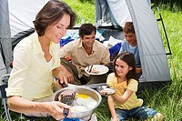 Family eating fried breakfast on camping trip, woman serving bacon to daughter 8-10 beside tent