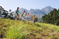 Family hiking on mountain trail, walking in line, boy 8-10 leading, side view