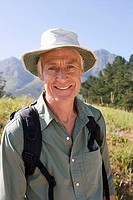 Senior man, with rucksack and sun hat, standing on hiking trail in mountains, smiling, close-up, portrait
