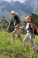 Senior couple, with rucksacks and sun hats, hiking on mountainside, holding hands, smiling, side view