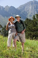 Senior hikers, with rucksacks and sun hats, standing on mountainside, arms around each other, smiling, portrait