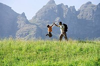 Father and son 8-10 hiking on mountain trail, boy jumping in air, giving man high five, profile