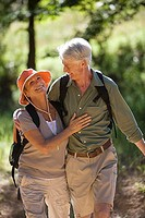 Senior couple, with rucksacks, hiking along woodland trail, arms around each other, smiling