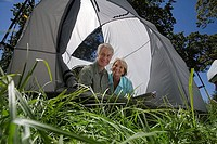 Senior couple sitting inside tent, smiling, portrait surface level, tilt