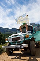 Young man sitting on roof of parked jeep on dirt track in mountain valley, consulting map tilt