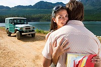 Young couple embracing near parked jeep on dirt track beside lake, woman smiling, portrait