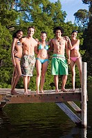 Five young adults, in swimwear, standing side by side on lake jetty, smiling, front view, portrait