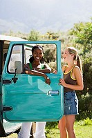 Two young women standing beside parked jeep, leaning on turquoise door, laughing, portrait