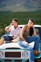 Young couple sitting on bonnet of parked jeep in mountain valley, man using mobile phone