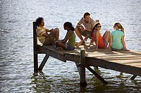 Five young adults relaxing at edge of lake jetty