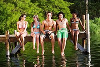 Five young friends, in swimwear, sitting side by side on lake jetty, front view, smiling, portrait