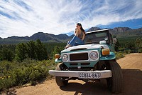 Solitary young woman sitting on bonnet of parked jeep on dirt track in mountain valley, looking at scenery