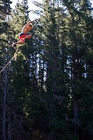 Teenage boy 12-14, in swimming shorts, swinging from rope above lake, side view, low angle view