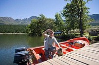 Senior man standing in moored motorboat beside lake jetty, tilting cap, admiring scenery, smiling