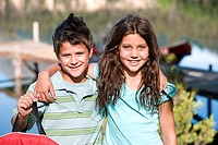 Boy and girl 7-10 standing side by side, arms around each other, smiling, front view, portrait