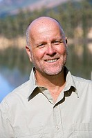 Mature man standing beside lake, smiling, close-up, front view, portrait