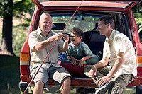Boy 8-10 sitting in boot of parked SUV with father and grandfather, senior man holding fishing rod, smiling