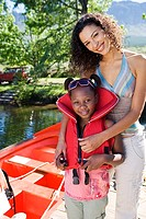 Mother and daughter 7-9 standing beside moored motorboat on lake jetty, girl wearing life jacket, smiling, portrait