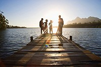 Family, in swimwear, standing at edge of lake jetty at sunset lens flare